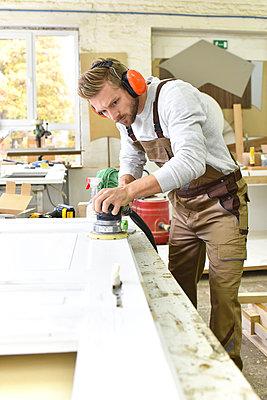Carpenter restoring a wooden door - p300m1192331 by lyzs