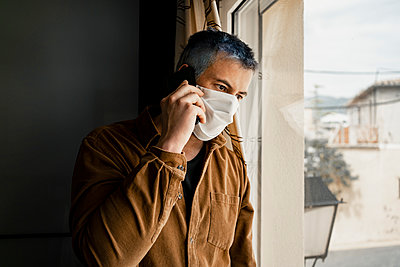 Man wearing protective mask and looking out of the window - p300m2189485 by Rafa Cortés