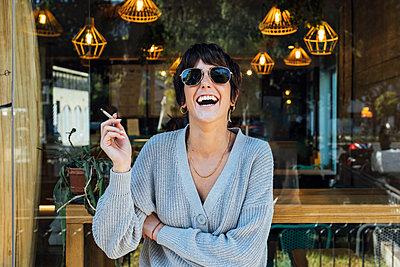 woman with sunglasses smoking a cigarrette - p300m2252407 von Julio Rodriguez