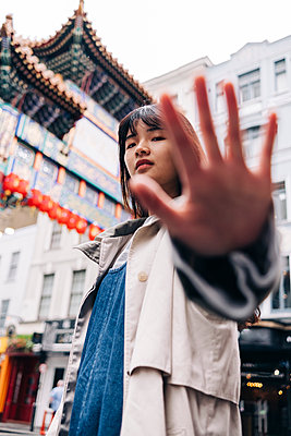 Young woman gesturing stop sign in city - p300m2298826 von Angel Santana Garcia