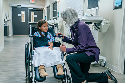 Doctor talking to girl in a wheelchair - p555m1521450 by FS Productions