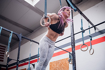 Young woman balancing on gymnastic rings in gym - p924m2097918 by Eugenio Marongiu