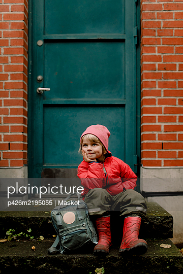 Thoughtful boy in warm clothing sitting on steps against door - p426m2195055 by Maskot