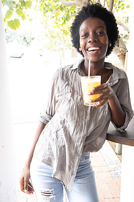 Young African woman has a soft drink - p1640m2260099 by Holly & John