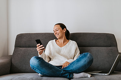 Smiling woman using smart phone while sitting with laptop on sofa - p300m2240177 by David Molina Grande
