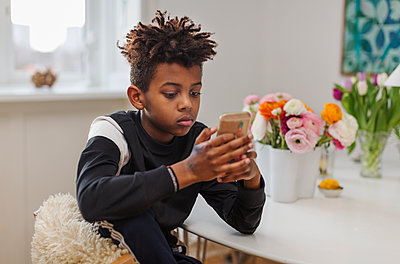 Boy using cell phone - p312m2139421 by Pernille Tofte