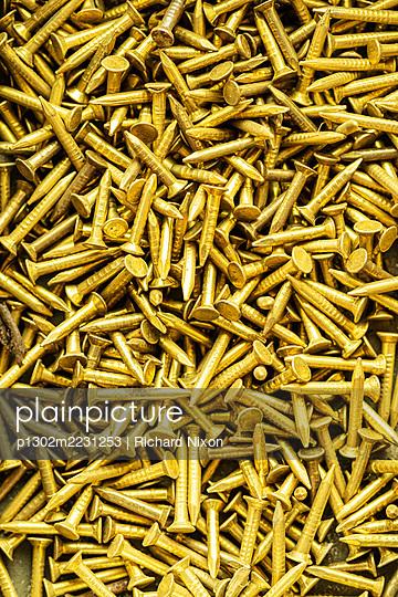 Close up of brass tacks or nails - p1302m2231253 by Richard Nixon