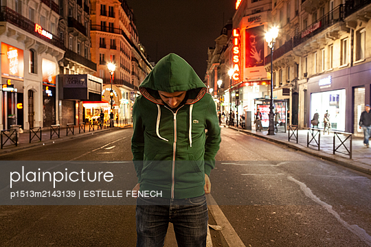 Young man in hoodie by night - p1513m2143139 by ESTELLE FENECH