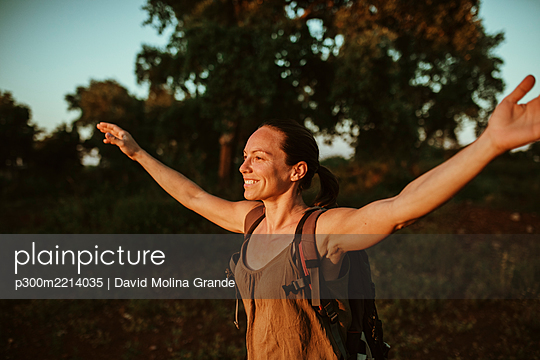 Smiling female trekker standing with arms outstretched in forest during sunset - p300m2214035 by David Molina Grande