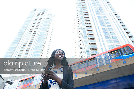 Smiling businesswoman with mobile phone against metro train and skyscrapers - p300m2241595 by Pete Muller