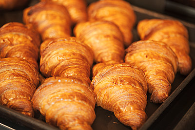 Close up of tray of freshly baked croissants in a bakery. - p1100m1530972 by Mint Images