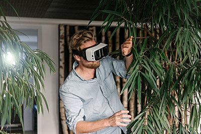 Man wearing VR glasses surrounded by plants - p300m1535688 by Joseffson