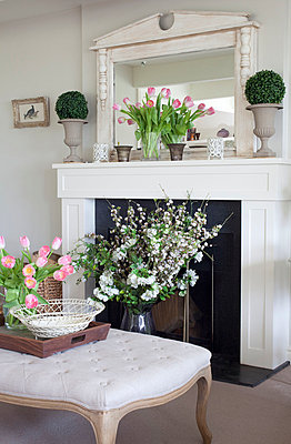 Cut flowers and ottoman at fireplace of Sussex home  UK - p3493565 by Robert Sanderson