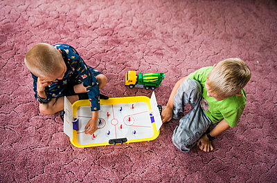 Caucasian brothers playing hockey game on floor - p555m1411158 by Aleksander Rubtsov