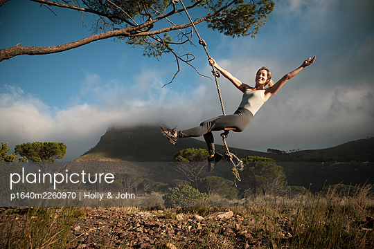 Blond woman swings on a rope in the mountains - p1640m2260970 by Holly & John
