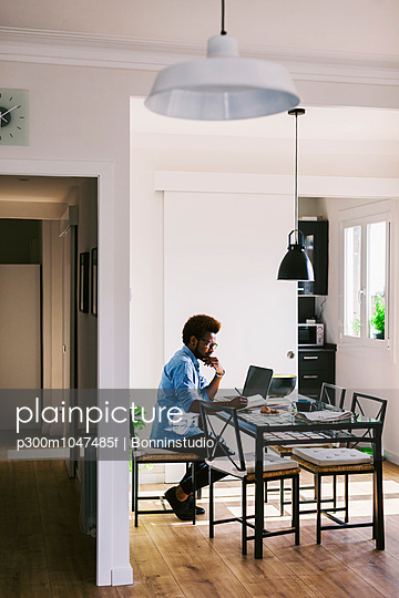 Young man working with laptop at home office - p300m1047485f by Bonninstudio