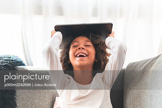 Portrait of little girl laughing on sofa with digital tablet in hands - p300m2242696 by Josu Acosta