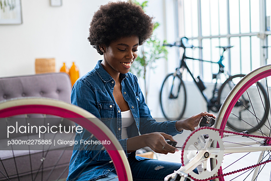 Smiling young woman repairing bicycle at home - p300m2275885 by Giorgio Fochesato