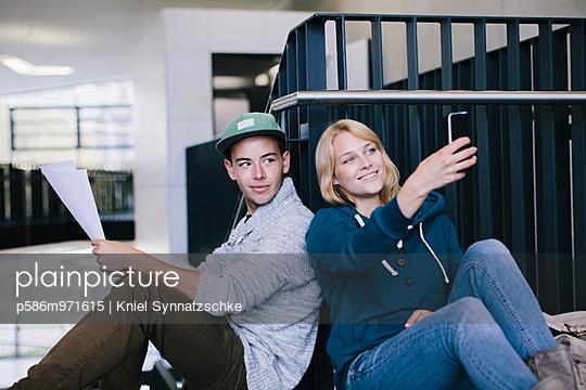 Junges Paar mit Smartphone im Treppenhaus - p586m971615 von Kniel Synnatzschke