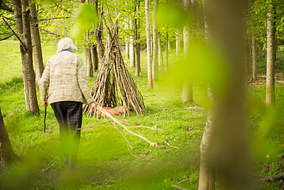 Senior woman making branch teepee in woodland - p1023m2201397 by Martin Barraud