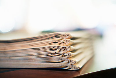 Stack of Newspapers at a Hotel in France - p1084m1036805 by GUSK