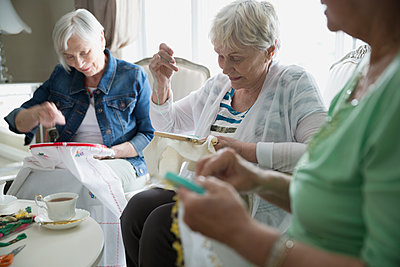 Senior women drinking tea and embroidering - p1192m1145589 by Hero Images