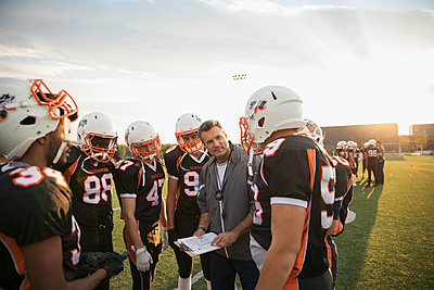 Coach with clipboard talking to teenage boy high school football team in huddle on football field - p1192m1500251 by Hero Images