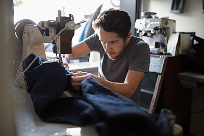 Focused male tailor using sewing machine in denim repair shop - p1192m2062554 by Hero Images