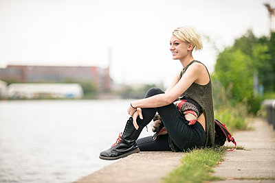 Smiling blonde woman relaxing at riverside - p300m1206036 by A. Tamboly