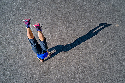 Aerial view of sportive young woman training handstand - p300m2004755 by Stefan Schurr