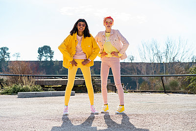 Two alternative friends wearing yellow and pink jeans clothes, posing - p300m2023779 by VITTA GALLERY