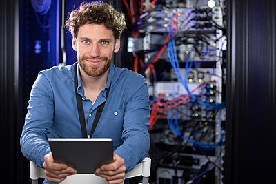 Male IT engineer with digital tablet sitting on chair in server room - p300m2274467 by Florian Küttler