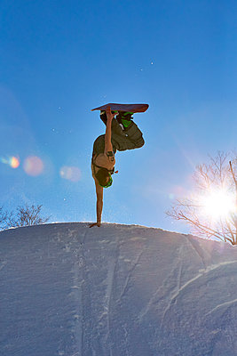 Snowboarder doing handplant trick, Vermont, USA - p343m1577979 by Josh Campbell