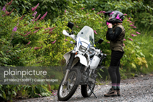 A women takes a break from motorcycle riding and takes off her helmet. - p1166m2136891 by Cavan Images