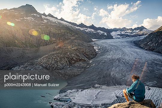Mann sitzt auf Stein und blickt auf Rhonegletscher, Furkapass, Obergoms, Wallis, Schweiz - p300m2243908 von Manuel Sulzer