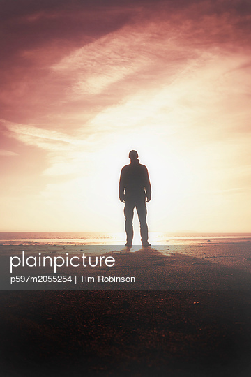 Silhouette man standing on beach with sun behind - p597m2055254 by Tim Robinson