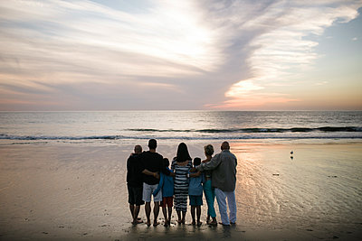 Rear view of family standing at beach against cloudy sky during sunset - p1166m1531325 by Cavan Images