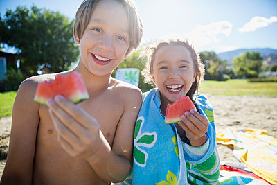 Portrait smiling brother and sister eating watermelon on sunny summer beach - p1192m1183789 by Hero Images