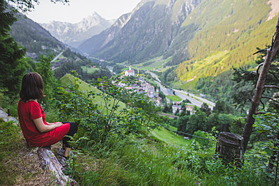 Young woman sitting on mountain above valley - p1427m2169332 by Oleksii Karamanov