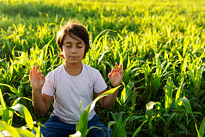 Boy meditating while sitting on grass in meadow - p300m2221327 by Valentina Barreto