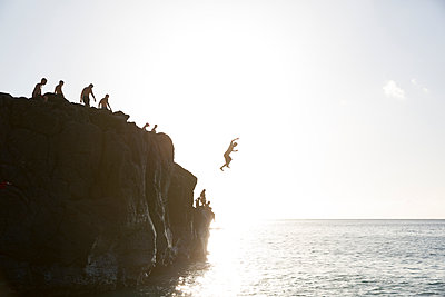 Friends jumping from cliff into ocean - p555m1491060 by John Duarte