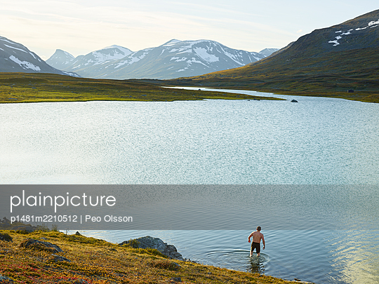 Man bathes in mountain lake, Lapland, Sweden - p1481m2210512 by Peo Olsson