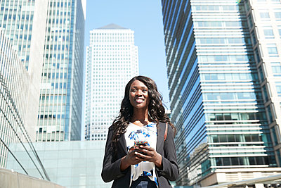 Smiling businesswoman using mobile phone while standing in city - p300m2241138 by Pete Muller