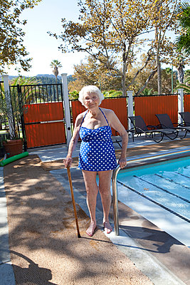 Older Caucasian woman standing with cane near swimming pool - p555m1408861 by Shestock