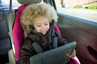 Mixed race girl using digital tablet in back seat of car - p555m1419543 by Inti St Clair photography