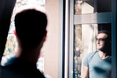 Window refection of a young man - p795m2063216 by JanJasperKlein