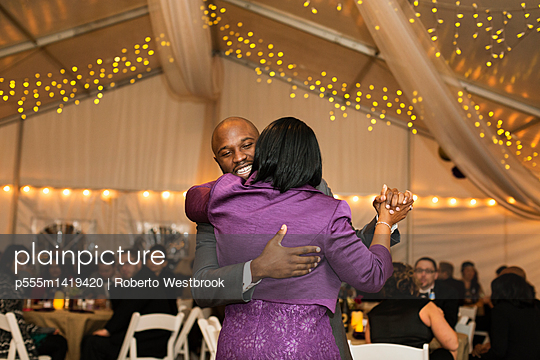 Black groom dancing with mother at reception - p555m1419420 by Roberto Westbrook