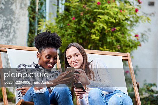 Smiling young friends using smartphones in park - p623m2294806 by Eric Audras
