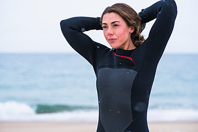 Young woman preparing to go winter surfing in snow - p1166m2177036 by Cavan Images
