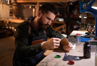 Craftsman applying glue on leather - p1166m2234426 by Cavan Images